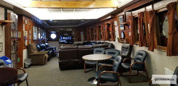 Grande salle avec fauteuils et télé